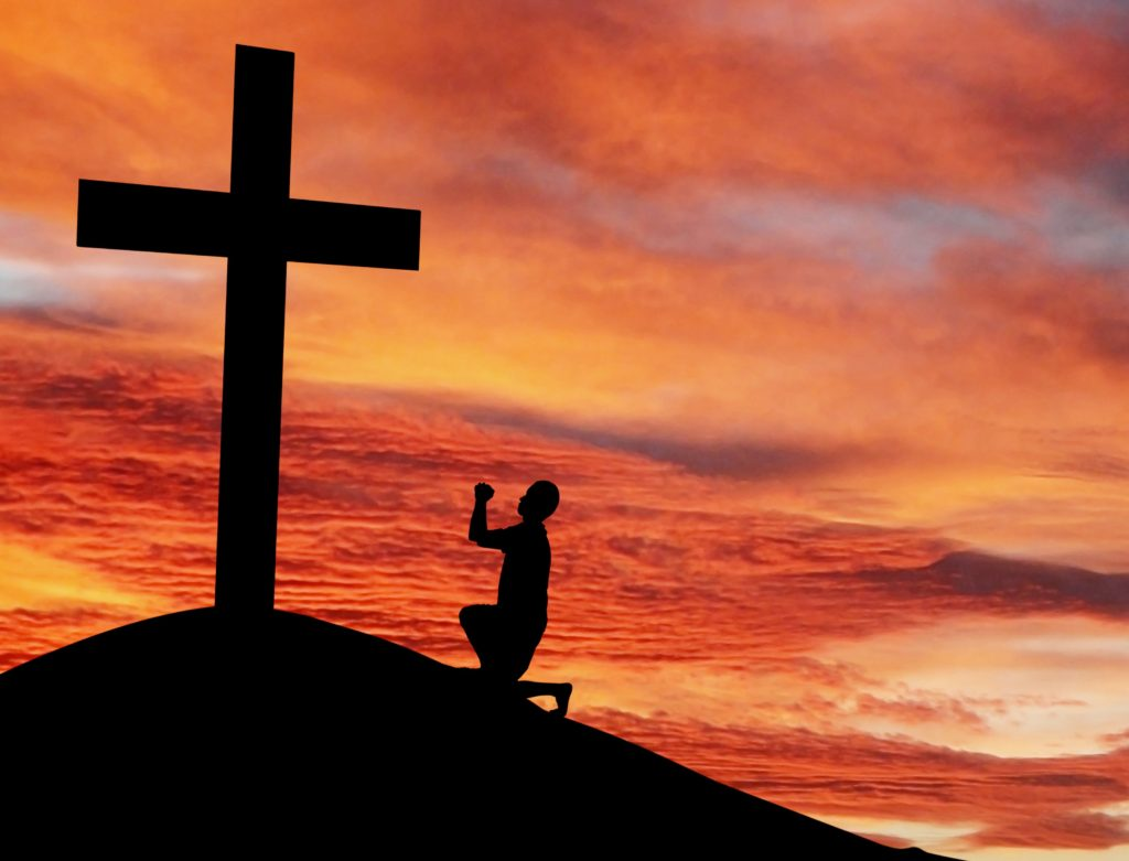 Christian background: Silhouette of a man praying by the cross at sunrise or sunset